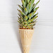 Ice cream cone with pineapple leaves on white background. Fruit and candy concept