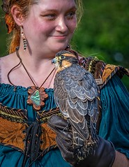 The Lady And The Falcon (Wes Iversen) Tags: aplomadofalcon falcofemoralis holly michigan michiganrenaissancefestival nikkor18300mm apprentice apprenticefalconer birds bokeh earrings falconry falcons people portraits smiles women