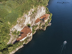 Eremo di Santa Caterina del Sasso - Leggiuno (Italy) (Andrea Moscato) Tags: andreamoscato italia montagna landscape light luce paesaggio sky shadow nature natura natural naturale view vista vivid day panorama lago lake water freshwater ombre yellow mountain boat orange house architecture architettura art overlook fly drone dji mavic air quadcopter blue dark deep buildings monte pier monument roof monastero green trees rock cliff white yacht