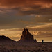 Lone photographer with tripod taking photos of the storm clouds at sunset over Shiprock volcanic rock formation near Shiprock, New Mexico
