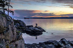 Saxe Point Sunset (Paul Rioux) Tags: saxe point esquimalt evening sunset clouds calm water reflection people ship rocks trees seashore waterfront prioux