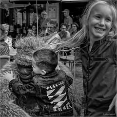 Play it smart (John Riper) Tags: johnriper street photography straatfotografie square vierkant bw black white zwartwit mono monochrome netherlands john riper fryslân makkum visserijdagen 2019 girl boy friesland frisian bokito monkey gorilla smile hug terrace fun zwvk