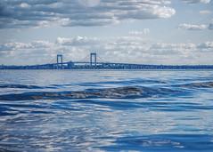 Throgs Neck Bridge in New York (Cordia Loretta) Tags: stripedbassday bridge throgsneckbridge bronx newyork water wake longislandsound sea ripple wave clouds cloudy blueskies cityisland tugboat tug sailboat sail
