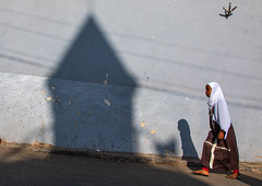 Ethiopian woman passing in front of the shadow of a mosque minaret in the street, Harari region, Harar, Ethiopia (Eric Lafforgue) Tags: africa children citylife cultures dailylife day domesticlife eastafrica ethiopia ethiopia2019104 fulllenght girls harar hararjugol harer harergey horizontal hornofafrica islam lifestyles muslim onegirlonly oneperson oromia outdoors photography realpeople shadow street traditionalclothing traveldestination unescoworldheritagesite harariregion