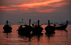 As the sun goes down: Longtails at Railay Beach, Thailand. (trev.eales) Tags: railaybeach railay railaybeachwest thailand beach tropicalbeach sunlight sunset longtail longtailboat longtailboats serene reflections boats clouds dusk andamansea southeastasia nikon treveales