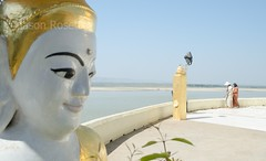 Buddha with pleasant smile in foreground, with river and guests behind (jasonrosette) Tags: camerado jrosette jasonrosette asia travel statue buddha water sunny river boats burma myanmar irriwaddy smile