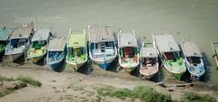 Row of Boats on bank of the Irriwaddy River, Burma (Medium View) (jasonrosette) Tags: camerado jrosette jasonrosette asia travel water shore river boats burma myanmar irriwaddy ferry riverine