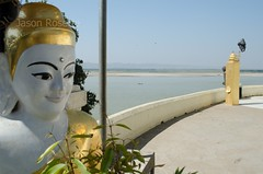 Buddha with pleasant smile in foreground, with river view behind