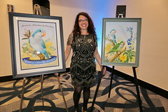 Tina Marie, the artist for this year, stnading next to her work. (QuakerVille) Tags: qps quaker parrots afa conference 2019 jonmarkdavey orlando hotelb afa2019qpsgroupshotsvarious lakebuenavista florida unitedstates