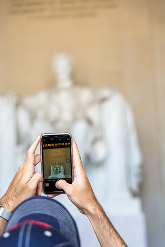 Tourist takes a photo of the Lincoln Memorial