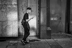 Mobile (Leanne Boulton) Tags: urban street candid streetphotography candidstreetphotography streetlife urbanlandscape young man male face expression mood atmosphere mobile smartphone phone walking sidewalk grit grime dirt dirty filth filthy gritty tone texture detail naturallight outdoor light shade city scene human life living humanity society culture lifestyle people citystreets modernliving canon canon5dmkiii 24mm wideangle ef2470mmf28liiusm black white blackwhite bw mono blackandwhite monochrome glasgow scotland uk