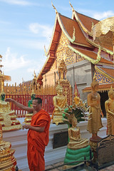 The Pagoda Of The Holy Relic Statues (peterkelly) Tags: digital canon 6d asia southeastasia gadventures indochinaencompassed thailand chiangmai watphrathatdoisutheprajaworawiharn thepagodaoftheholyrelic mainwiharn monk gold statue blue sky roof buddha buddhism