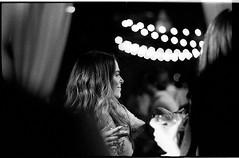 JamieClarkWeddingFilm218 (Johnny Martyr) Tags: wedding reception black white film 35mm nikon nikkor fm2 fm2n 85mm 18 bokeh out focus points light oof dof depth field girl woman drink party foreground isolated portrait candid documentary photojournalism string lights mt washington dye house baltimore maryland grain grainy tmax p3200 kodak hc110 hc110b