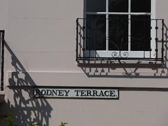 Rodney Terrace - Rodney Road, Cheltenham - sign (ell brown) Tags: cheltenham cheltenhamspa gloucestershire england unitedkingdom greatbritain spatown tree trees rodneyrd rodneyterrace sign gradeiilistedbuilding gradeiilisted terraceof21houses 1555rodneyrd stuccooverbrickwithslateroof