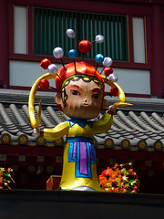 At the Singapore Chinatown Market (Steve Taylor (Photography)) Tags: horns market hat baubels balls lanternfestival roof colourful lady woman asia singapore flower chinatown