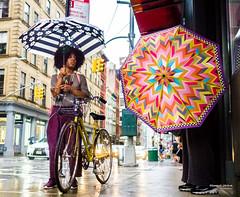 The New Yorkers - Rain shield (François Escriva) Tags: street streetphotography us usa nyc ny new york people candid olympus omd photo rue light woman colors sidewalk manhattan rain shield unmbrella pink fun funny blue green yellow bike raining