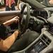 Mann sitzt im Ausstellungsfahrzeug von Porsche: E-Auto Taycan Turbo S mit Powermeter, zentraler Tempoanzeige und Touch-Bedienfeld