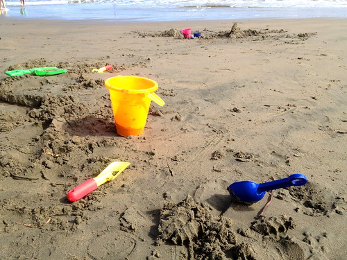 children's plastic bucket and scoops,  on wet sandy pacific ocean beach