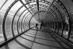 Shadows (Croydon Clicker) Tags: monochrome bw blackwhite whiteblack greyscale people passengers luggage cases trollies bridge arches circles shadows sunshine poplar london nikon tokina