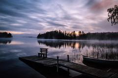Misty daybreak (mabuli90) Tags: lake finland boat dock mist fog morning dawn water grass forest tree wood bench clouds sky sunrise