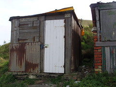 Shed run (Nekoglyph) Tags: skinningrove cleveland beach rust metal wood door white corrugated huts sheds cliff hill grass green square bricks yellow roof