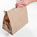 Man holding a brown paper bag in his hand