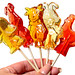 Sugar candies in the form of animals and cartoon characters on sticks in the hand