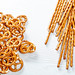 Top view salted straws and pretzels on white wooden background