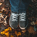 Feet in shoes on fallen dry leaves