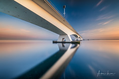 The Water Is Always Deeper Than What It Reflects I (Alec Lux) Tags: m15 architecture blue bluehour bridge coast coastline curves design exterior golden goldenhour haida haidafilters holland lines longexposure minimal minimalism modern netherlands ocean outdoor outside reddiamond reflection sea seascape shape sun sunset symmetry zeeland