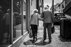 In Sickness and in Health (Leanne Boulton) Tags: urban street candid streetphotography portrait candidstreetphotography streetlife sociallandscape old elderly man woman male caring female couple assistance help helping carrying uphill struggle ageing tone texture detail depthoffield bokeh naturallight outdoor light shade shadow city scene human life living humanity society culture lifestyle people canon canon5dmkiii ef2470mmf28liiusm black white blackwhite bw mono blackandwhite monochrome glasgow scotland uk