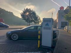 Tesla Model S im Sonnenlicht ladend an einer Autobahnraststätte