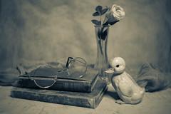 Still Life (DayBreak.Images) Tags: tabletop stilllife vintage antique books glass vase flower rose ceramic duck figurine cheese cloth canondslr lensbabyburnside35 ringlight lightroom splittone