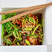 Soba noodles with mushrooms, broccoli, carrots, peppers, leeks, asparagus and sesame closeup. Top view