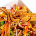 Buckwheat noodles with mushrooms with sweet and sour sauce close-up on chopsticks