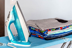 Electric iron on an ironing board with a stack of ironed clothes (wuestenigel) Tags: electric clothing textile domestic closeup concept home background folded appliance board cotton household pile blue laundry housework iron cloth ironing clothes room wäsche hausarbeit noperson keineperson family familie job travel reise color farbe beach strand equipment ausrüstung laundryfacility wäscherei messy unordentlich fashion mode bookbindings buchbindungen business geschäft clean reinigen vacation urlaub plastic kunststoff wear tragen indoors drinnen stilllife stillleben 2019 2020 2021 2022 2023 2024 2025 2026 2027