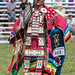 Robed in Cherokee fancy attire, a woman under the hot summer sun awaits the drums to start off the golden age class of the pow wow competition