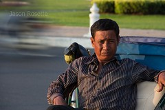 Cyclo Driver Waits for Customers with Passing Traffic Background (#1)