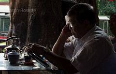 Man in Phnom Penh Reads His Tablet at Coffee Stand