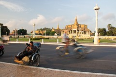 Wide view of a cyclo Driver Waits for Customers with Passing Traffic Background (#1)