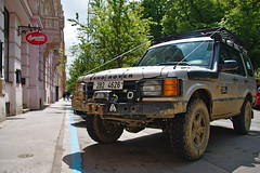 (Debarshi Ray) Tags: czech brno summer city canon canoneos70d tamron tamronaf18270mmf3563 cars car vehicle automobile motorcar landroversuvsports utility vehiclemudnational geographic tyre black orange red budweiser pub pavement footpath building houses trees green leaves