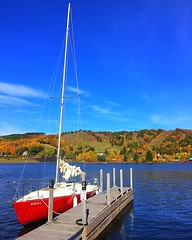 Fall colors and a sailboat (35adventuresblog) Tags: michigan fall autumn colors leaves hill trees forest sailboat red dock water lake river boat