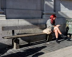 Red on the edge (sasastro) Tags: redhair woman legs boots bench mobilephone norwich street streetphotography sunlight
