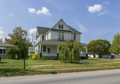 House — Paulding, Ohio (Pythaglio) Tags: house dwelling residence historic twostory balloonframe woodsiding 11windows porch sidewalk bushes trees clouds paulding ohio pauldingcounty