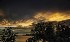 Departing Storm (Jeff Saly) Tags: sun sunset storm weather lake light beautiful canada trees nature landscape