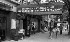 Ukrainian National Home (neilsonabeel) Tags: nikonfm2 nikon nikkor film analogue blackandwhite restaurant sign awning ukrainiannationalhome eastvillage manhattan newyorkcity street
