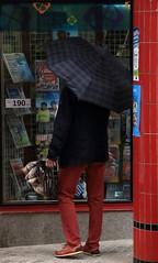 Flânerie pressée... (Tonton Gilles) Tags: alençon normandie maison de la presse vitrine magazines personnage badaud silhouette parapluie rouge colonne scène rue