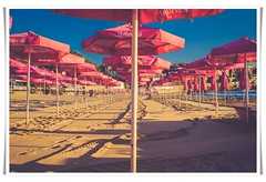 Parasols on beach... (Edenimage) Tags: people film beach coast sand sun sky warm warmth parasols umbrellas shade shadow pink blue yellow vacation holidays seaside tan outdoors outside nopeople