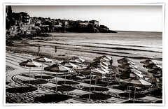 1960's? Black sea resort... (Edenimage) Tags: people film beach parasols sand sun sea sky blackandwhite old retro umbrella outside shade shadow rocks coast seaside swim water waves house buildings architecture nature