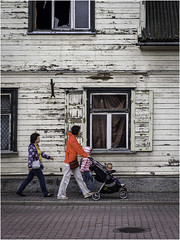 A young family has no attention for the dilapidated house (Luc V. de Zeeuw) Tags: childeren dilapidated house stroller walking window woman ventspils latvia